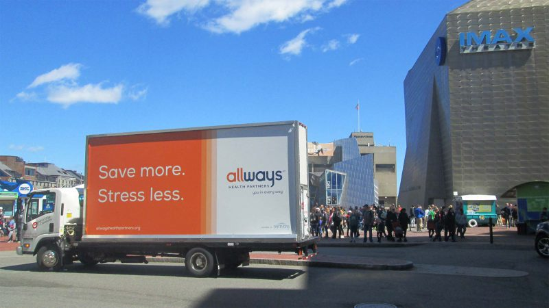 Billboard truck stopped in front of the New England Aquarium in Boston