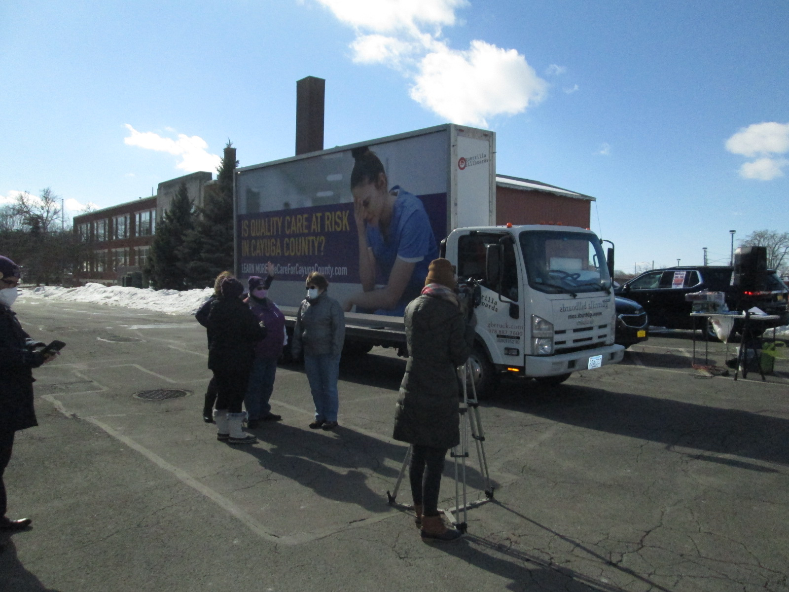 Billboard truck serving as a backdrop for TV reporter interviews.