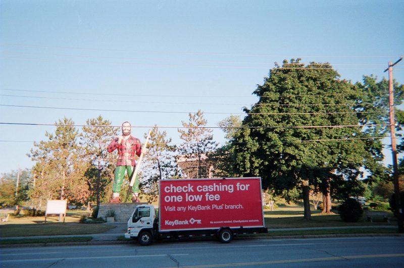 Billboard truck stopped in front of lumberjack statue in Bangor ME
